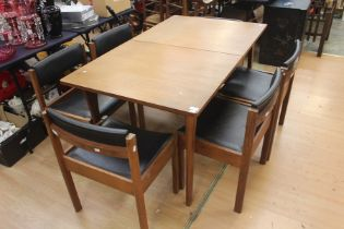A 1970s teak dining table and a set of six chairs, the table having a fold-out leaf, measuring