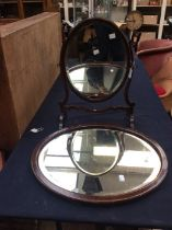 An Edwardian style stained wood oval shaped dressing table mirror and an oval wall mirror (2)