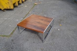 A 1970's rosewood coffee table in a Scandinavian manner, in a rectangular shape, raised on chrome