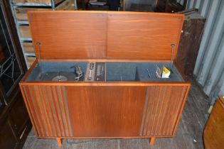A mid 20th century record player, two moulded edge panel lifting lids opening to two turntables,