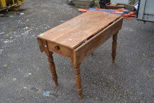 A 20th Century pine drop leaf table, measuring 75cm high, 100cm wide, 56cm deep