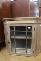 An early 20th Century beech and pine glazed hanging corner cupboard, 57cm high, 63cm wide