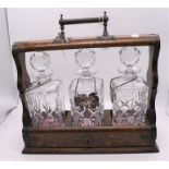 An early 20th century Tantalus fitted with three square decanters.