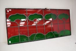 A stained glass panel in an Arts and Crafts style, 53 x 118cm, glazed to rear