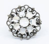 A silver and moonstone brooch by Bernard Instone, circular form claw set to the centre with a