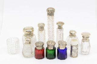 A collection of silver mounted cut & facet cut scent / toilet bottles, various dates and makers (