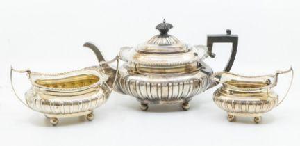 An Edwardian three piece silver tea set including teapot, sugar bowl, cream jug, shell and scroll
