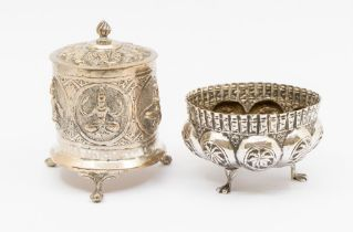 An Asian white metal lidded pot standing on 3 paw feet embossed with Deities etc., together with a