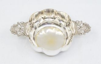A Victorian Twin handled silver bowl in a lobbed porringer style with ornate mask head handles