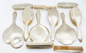 A quantity of 20th Century silver mounted dressing table sets, various dates and makers (Q)