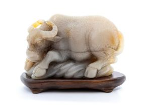 A pale beige and grey soapstone carving of a buffalo,the animal recumbent on a bank, with his