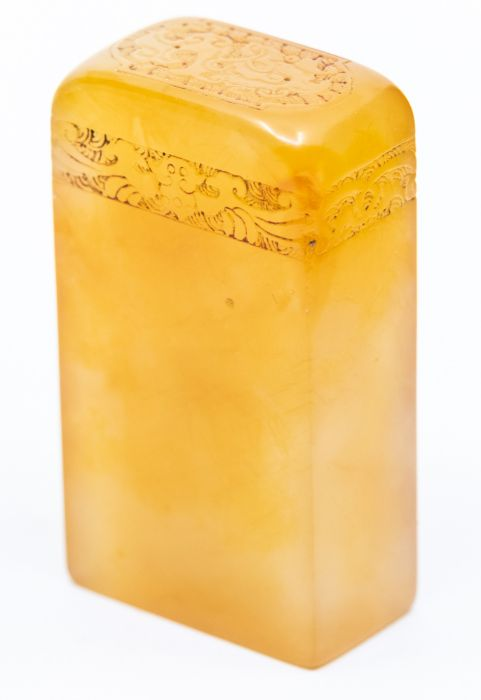 An orange jelly stone seal,the top carved with a band of carved foliage, the stone of a deep
