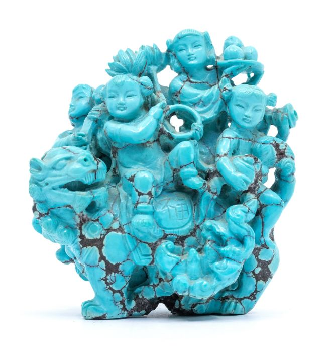 A Chinese turquoise matrix carved group,depicting four children seated on the back of a lion