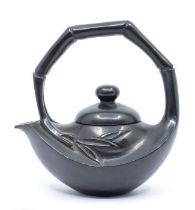 A black shousan stone teapot and cover,carved with a simulated bamboo overstrung handle, over a