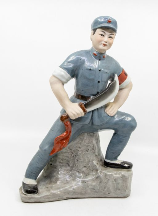 A Chinese Communist porcelain figure,standing with one foot raised on a rocky outcrop, holding a