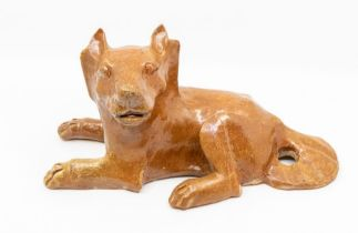 A Chinese brown glazed pottery figure of a dog,the animal reclining, with its head turned to the