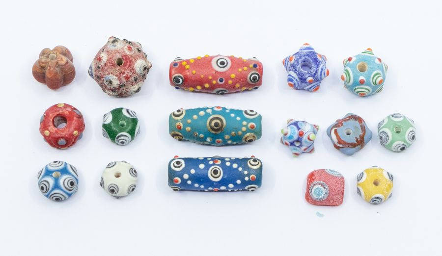 A group of Phoenician or Carthaginian coloured glass beads, each decorated in relief with eyes,