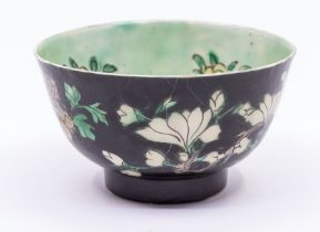 A Chinese famille noire bowl,the exterior painted with branches of peony and magnolia amongst