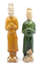 A pair of glazed Chinese pottery figures, each figure standing with their hands in front of their