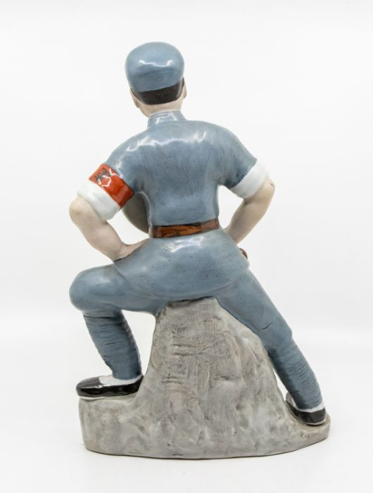 A Chinese Communist porcelain figure,standing with one foot raised on a rocky outcrop, holding a - Image 2 of 3