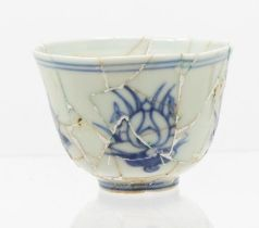 A Chinese blue and white 'lotus' cup,the gently rounded sides rising form a short foot, to a