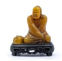 A soapstone carved figure of a luohan,the figure clad in flowing robes, with a tied sack to his