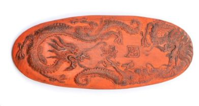 A Chinese cinnabar oval ink cake, Qing dynasty,the upper surface moulded with two dragons and