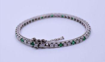 A white metal diamond and emerald bracelet, grain set thirty-four round brilliant-cut emeralds,