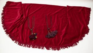 A large red velvet table cloth with large rope fringing. A pair of rope tie backs with tassels in