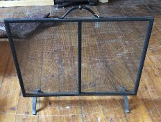 A black wrought iron fire screen, with carrying handle and pierced metal work screen, rasied on four