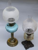 An Edwardian paraffin lamp with blue satin glass reservoir and reeded brass column, together with