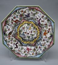 A reproduction French faience octagonal charger, decorated with panels of animals and flowers,