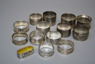 A collection of fourteen hallmarked silver and other white metal serviette rings, various dates
