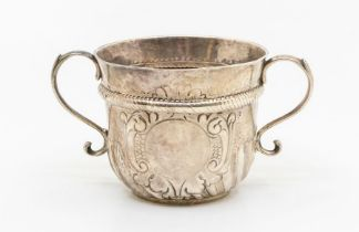 A Queen Anne Britannia standard silver two handled porringer, rope twist band above wyvern fluted