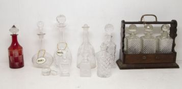 A Victorian stained wood tantalus with key and three moulded glass spirit decanter, together with