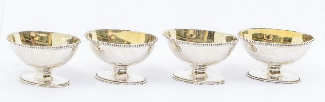 A matched set of four George III silver salts, boat shaped with beaded rims, engraved festoon