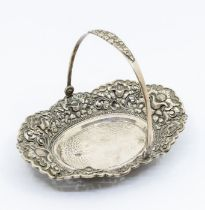 An 800 standard silver bon bon bowl with swing handle, the raised side chased with flowers, hammered