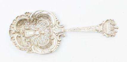 A Dutch style straining spoon, the centre bowl decorated with milkmaid within latticework, ornate