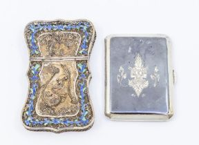 A Thai white metal filigree and blue enamel shaped cigarette case, the front and back decorated with