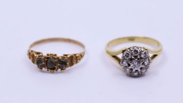 An 18ct diamond cluster ring, the central round brilliant-cut of approx. 0.10 ct with boorder of