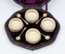 A set of four Victorian silver salts, cauldron shaped plain beaded rims, the bodies chased with