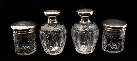 A matched four piece George V silver mounted and cut glass toilet set comprising two large bottles