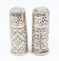 A pair of Victorian silver casters, domed pierced covers with engraved decoration, the bodies