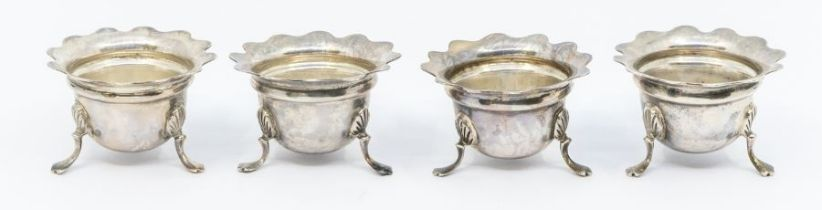 A set of four Edwardian silver salts, flared rims on three shell and trefid feet, hallmarked by