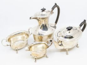 A George V silver four-piece tea set comprising teapot, hot water pot, milk and sugar, flared wavy