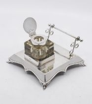 A George V silver combination inkstand and pen holder, plain shaped square body with wavy apron on