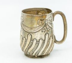 An Edwardian silver Christening mug, the body chased with ribbon tied swags above wyvern fluted