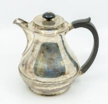 A George VI silver hot water jug, pear shaped body with ribbed section, ebonised handle and