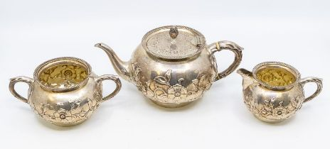 A Victorian Aesthetic silver three piece tea service, comprising teapot, milk jug and sugar bowl,