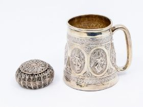 An Asian silver probably 800 standard tapering mug, the sides chased with ornate oval panels with
